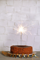Tasty cake with sparkler on wooden table