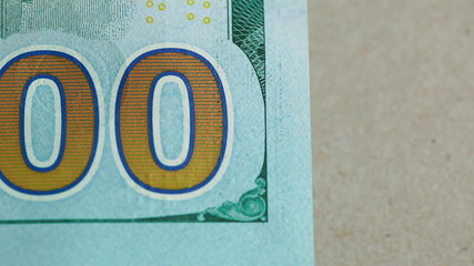 Close up macro slide shot of 100 on the one hundred dollar bill