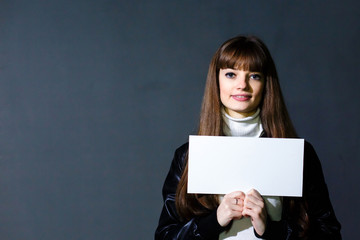 Young women holding empty white blank card on a dark wall backgr