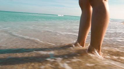 Ocean waves washing over woman's feet