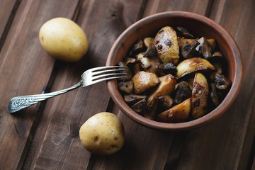 Ceramic bowl with roasted potato slices and mushrooms, close-up