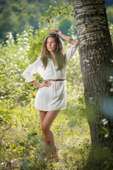 Attractive young woman in white short dress posing near a tree