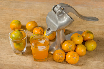 Glass of orange juice and Juicer  on wooden table