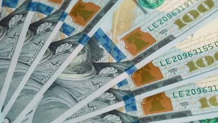 Spinning pile of 100 dollar bills close up
