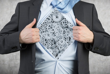 businessman tearing his shirt with gray gears