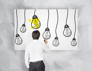 businessman drawing bulbs