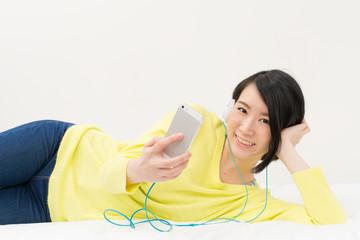 スマートフォンで音楽を聞く女性