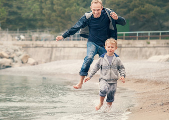 Father with son running on the sea surf line