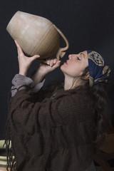 donna con scialle e capo coperto beve da un' anfora