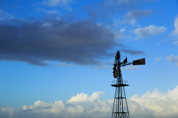 American windmill and a sky with different clouds.