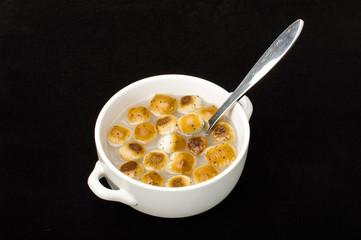 Kūčiukai in the white bowl isolated on the dark background