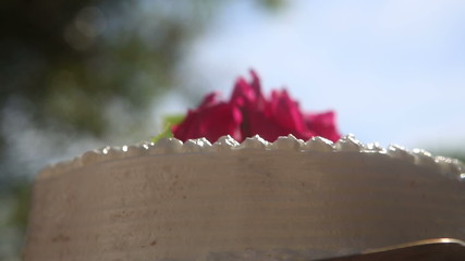 three red roses on the top of white creamy delicious cake
