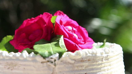 white creamy delicious cake decorated with three red roses