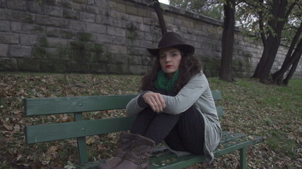 Lonely woman sitting on bench, steadycam, slow motion shot