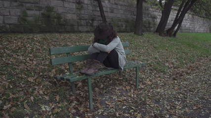 Woman sitting alone on bench, steadycam, slow motion shot