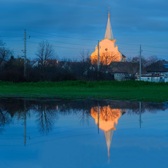 Dorfkirche am Abend spiegelt sich im Teich