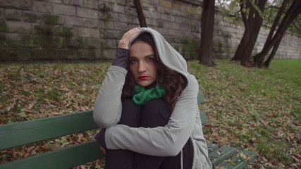Sad woman in hoodie looking to camera, steadycam, slow motion
