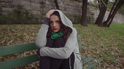 Sad woman in hoodie on bench, steadycam, slow motion shot
