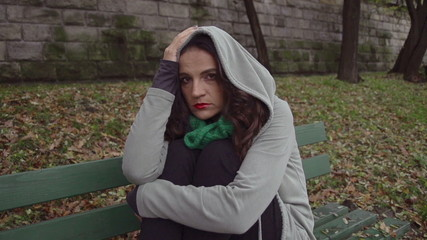 Sad woman in hoodie sitting on bench, steadycam, slow motion