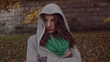 Sad woman wearing hoodie in park, steadycam shot, slow motion