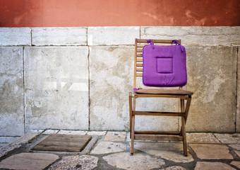 One wooden chair in a mediterranean alleyway