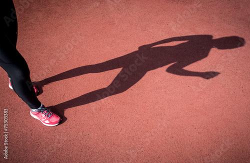 Fototapeta photo of shadow of running woman on running track