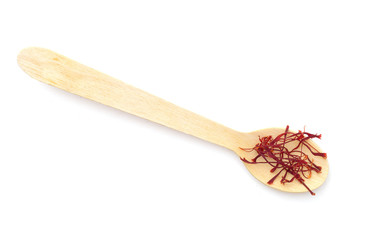 Saffron spice on small spoon, isolated on white background
