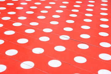 White spots on red floor for background.