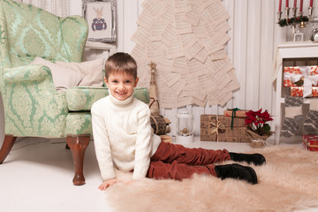 Little boy on carpet in Christmas interior