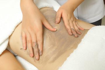 Beautiful girl having clay body massage