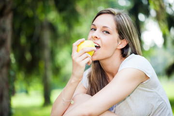 Woman eating an apple in the park