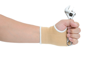 Man hand with wrist-support protection holding wrench on white b