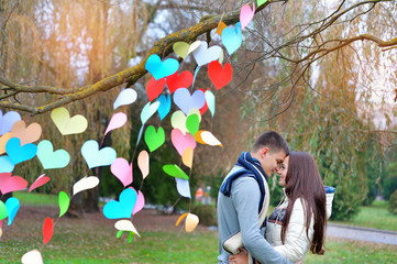 man and woman in the park on Valentine's Day, the tree is decora
