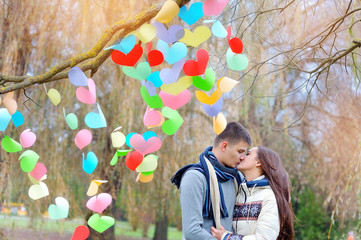 man and woman kiss on Valentine's Day, the tree is decorated wit