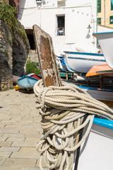 Boat and ropes Riomaggiore village on cliff rocks and sea