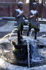 Brunnen mit zwei Schulkindern im Winter