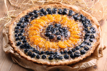 Tart with mandarins and cranberries on wooden background