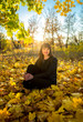 brunette woman sitting on grass at autumn park at sunny day