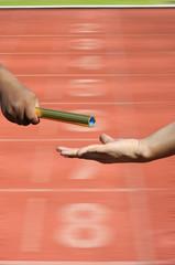Relay-athletes hands sending action on blur race track  startin
