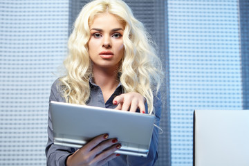 Blond woman using electronic tablet at home