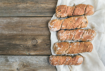 Freshly baked rustic village bread (baguettes) set on rough woo