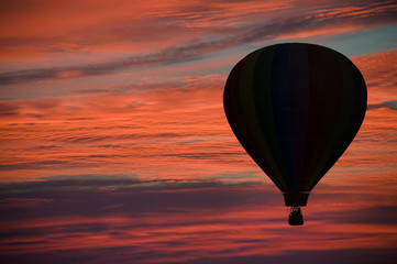 Hot-air ballooning among pink and orange clouds