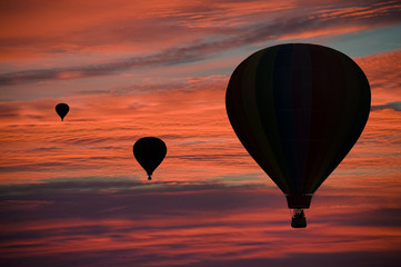 Hot-air balloons floating among clouds at dawn