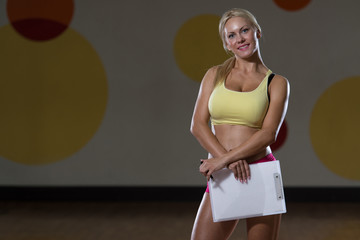 Personal Trainer With A Pad In Her Hand