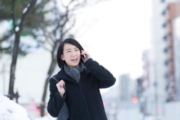 冬の街で電話する女性