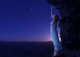 Young woman standing on cliff's edge of another planet.