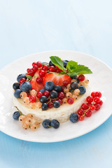 mini cheesecake with fresh berries on blue background, vertical