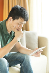 Asian young adult man using tablet and relax on sofa.