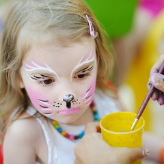 Adorable girl getting her face painted