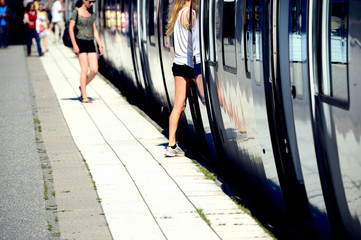 Anynomized woman enter train through open doors